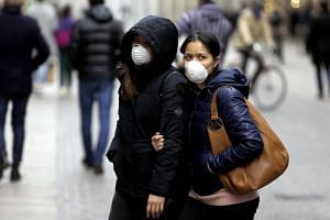 Two women wearing protective face masks walk in Milan, northern Italy, Feb 27 2020.
