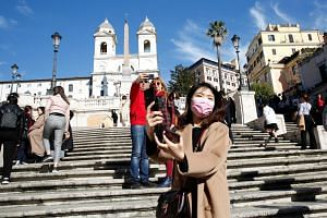 A tourist wearing protective a mask takes a selfie along the Spanish steps in Rome, Italy, on Feb 25, 2020. More than 50 per cent of hotel bookings in Rome have been cancelled until the end of March.