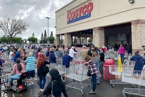 Shoppers line up outside a Costco to buy supplies in Honolulu, Hawaii, on Feb 28, 2020.