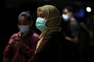 Passengers wearing protective masks wait for a commuter train at a station, following the outbreak of the coronavirus in Kuala Lumpur, Malaysia, on March 3, 2020.