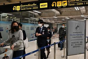 Passengers wearing protective face masks at the arrival area of Suvarnabhumi Airport in Bangkok, Thailand, on Feb 23, 2020.
