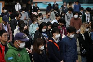 People with protective face masks in a moment of silence during a memorial service at Hibiya Park in Tokyo, on March 11, 2020.