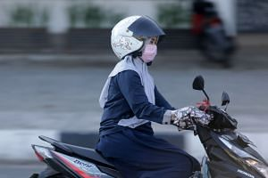 A motorist wears a protective face mask while driving, in Banda Aceh, Indonesia, on March 10, 2020.