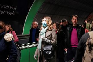 A person is seen wearing a protective face mask on the London Underground in London, Britain, on March 15, 2020.