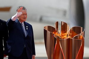 Tokyo 2020 Olympics president Yoshiro Mori waves next to the Olympic cauldron in Japan on March 20, 2020.