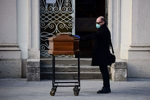 A man touches the coffin of his mother during a funeral service in the closed cemetery of Seriate, near Bergamo, Lombardy, on March 20, 2020.