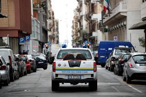 A civil protection car circulates to spread a message to invite people to stay at home in Bari, Italy, on March 27, 2020.