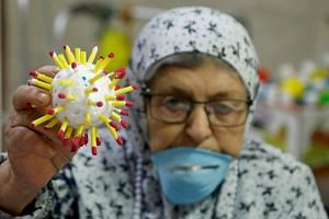 An elderly woman at a Palestinian nursing home in the Israeli-occupied West Bank holds up a coronavirus model.