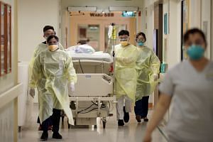 Healthcare workers in the Singapore General Hospital isolation ward assisting in the transfer of a suspected Covid-19 patient to an isolation room.