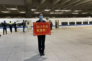 A staff member holds up a welcome sign at Hankou Railway Station in Wuhan, China.