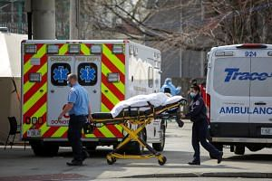 Emergency medical services workers transport a patient to Roseland Community Hospital in Chicago, Illinois, US, on April 7, 2020.