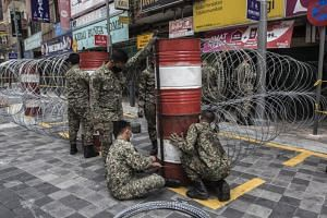 Malaysian army officers set up a barb wire fence in Kuala Lumpur on April 7, 2020.