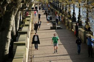 People walk, run and jog along River Thames in central London.