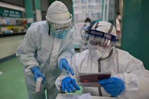 Medical workers check information as they take swab samples in Wuhan on April 16, 2020.