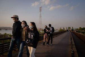 People walking over a bridge before the Han river and city skyline, in Seoul, on April 25, 2020.