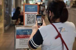 A shopper scans a QR code via SafeEntry at FairPrice Finest Junction 8 on April 30, 2020.