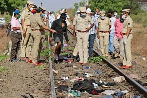 Police officers at the accident site after a goods train ran over 14 migrant workers in the western Indian state of Maharashtra yesterday. The men, who were among millions left destitute by the nationwide lockdown to stem the spread of the coronaviru