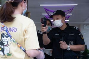 A security guard checks the body temperature of a woman in Wuhan on May 11, 2020.