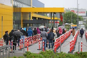 Customers wait outside an IKEA shop in Berlin on May 11, 2020.