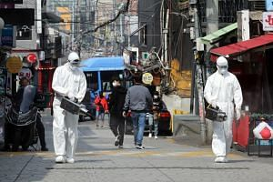 Quarantine workers spraying disinfectant around nightspots in Itaewon, Seoul, on May 11, 2020.