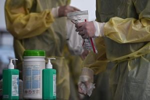 A medical worker holds onto a sealed bag with a tested swab, on May 15, 2020.