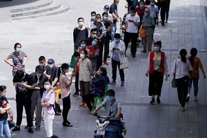 Residents wearing face masks queue for nucleic acid tests in Wuhan on May 16, 2020.