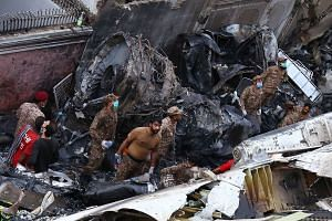 Rescue workers search the wreckage of the passenger plane in Karachi, Pakistan, on May 22, 2020.