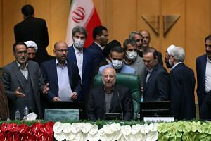 Mohammad-Bagher Ghalibaf (seated) was elected speaker of Iran's parliament on May 28.