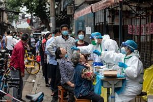 Medical workers take swab samples from residents in Wuhan on May 15, 2020.