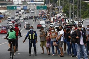 Commuters wait to get a ride along a road in Quezon City, the Philippines, on June 1, 2020.