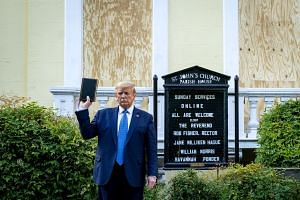 Trump holds a Bible, for a photo opportunity, as he stands outside the boarded up St John's Episcopal Church.