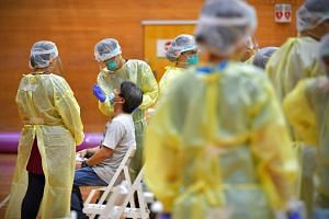 A man gets a swab test done at the Bukit Gombak Sports Hall on June 9, 2020.