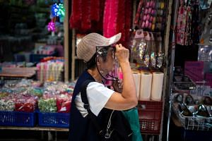 A woman wearing a face shield shops at a wholesale market in Bangkok on June 10, 2020.