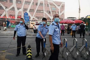 Chinese police block the entrance of the Xinfadi meat wholesale market in Beijing on June 12, 2020.