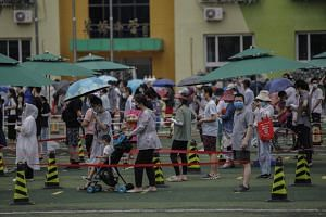 Residents queue at a makeshift coronavirus testing centre in Beijing, on June 18, 2020.
