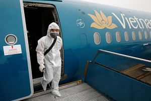 A health worker steps out of a Vietnam Airlines plane after spraying disinfectant during the coronavirus outbreak, at Noi Bai airport in Hanoi, Vietnam, on Feb 21, 2020.