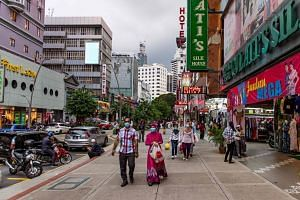 People walking along a shopping area in Kuala Lumpur on May 21, 2020.