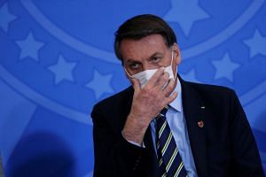 Bolsonaro adjusts his protective face mask during an event in Brasilia, June 17, 2020.