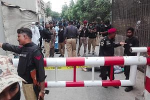 Above: Police officers securing an area around a body outside the Pakistan Stock Exchange after a group of gunmen from the Balochistan Liberation Army opened fire and hurled a grenade at the building in Karachi yesterday. Right, above and below: An o