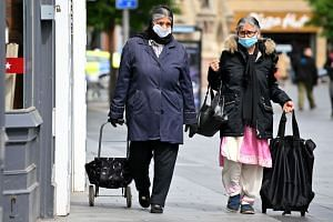 Shoppers walk in the city centre of Leicester, June 30, 2020.