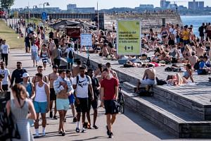 People stroll, sunbathe and swim at a bathing jetty during a heatwave in Malmo, Sweden, on June 25, 2020.