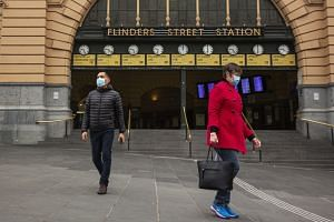 People walking outside Flinders Street Station in Melbourne, Australia, on July 17,  2020.