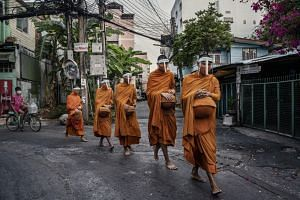 Monks from Wat Matchanthikaram receive alms from local residents in Bangkok on April 22, 2020.