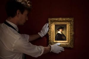 A Sotheby's assistant holds the self-portrait by Dutch artist Rembrandt in London.