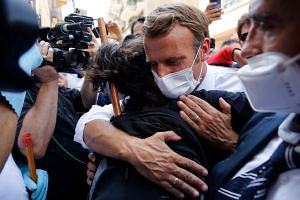French President Emmanuel Macron hugs a resident as he visits a street in Beirut, Lebanon, on Aug 6, 2020.