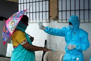 A healthcare worker checks the temperature and pulse of a resident during a check-up camp for the coronavirus, in Mumbai, India, on July 4, 2020.