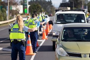 Police officers wearing protective masks signal to motorists at a checkpoint in the Bombay area of Auckland, New Zealand.