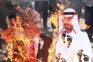 Palestinians burn cutouts depicting Abu Dhabi Crown Prince Mohammed bin Zayed al-Nahyan and Israeli Prime Minister Benjamin Netanyahu, during a protest against the peace agreement in the West Bank city of Nablus, Aug 14, 2020.