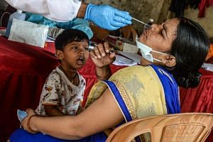 A boy watches as a health worker collects a nasal swab from his mother during a coronavirus screening in Mumbai on Aug 19, 2020.