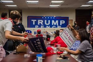 People grab signs to show support for US President Donald Trump as they watch his acceptance speech at the Republican National Convention, on Aug 27, 2020.